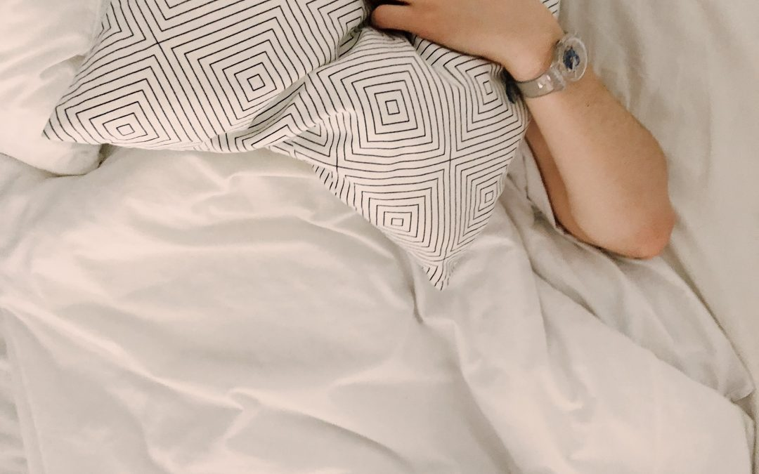 woman in bed hiding behind white pillow